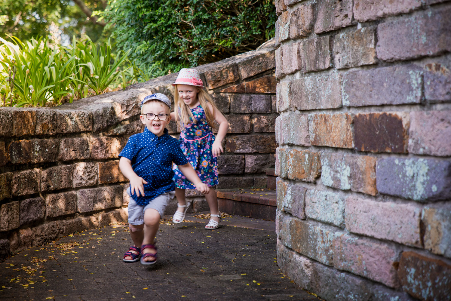 Kids running down stairs in traditional cottage garden. Outdoor family photos Caboolture Photographer Family Photography