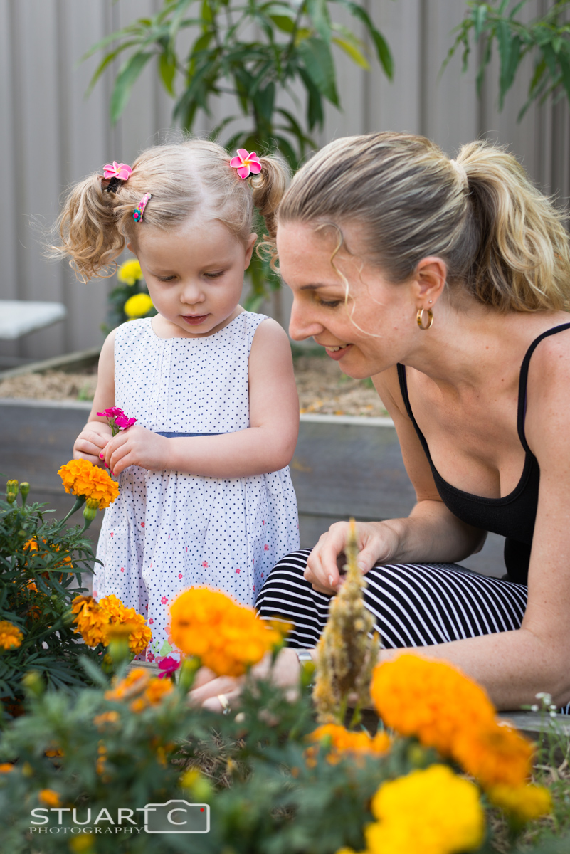 Mother and Daughter picking flowers in their backyard vegie patch