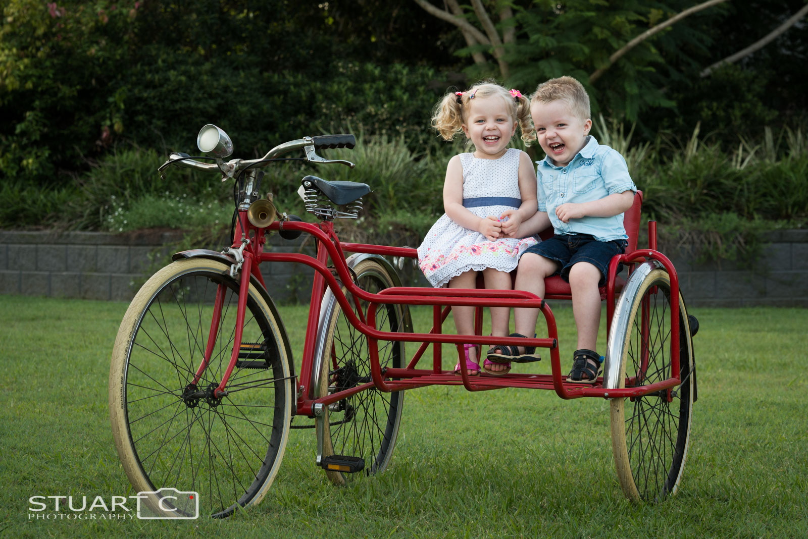Siblings, children, kids sitting on vintage push bike with side car