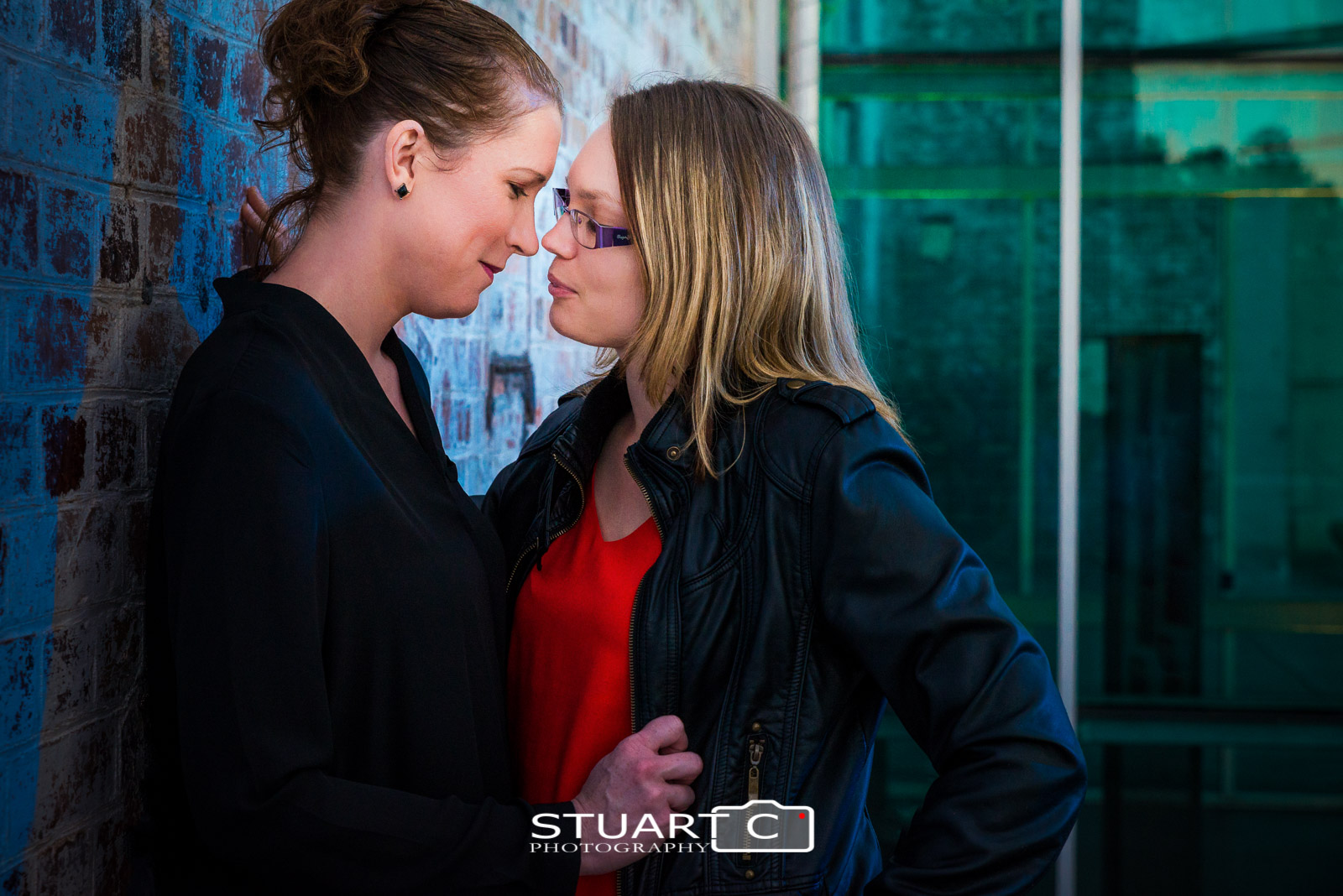 Female couple in black jackets against brick wall with green glass behind during evening