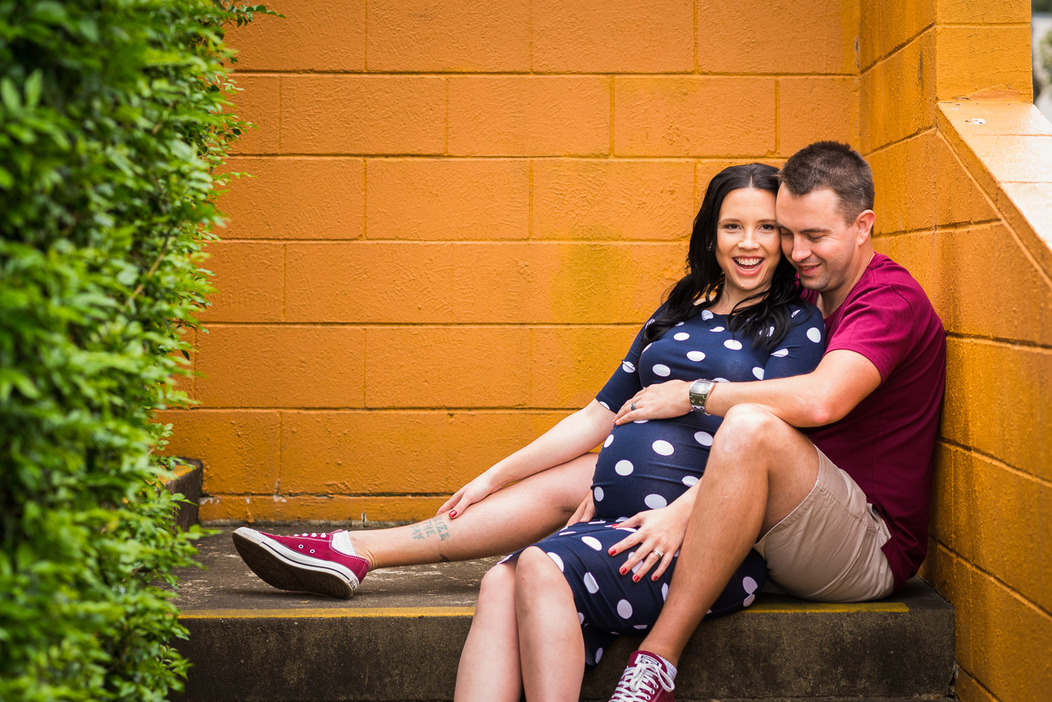 Maternity Portrait of couple sitting on step in front of bright yellow brick wall in urban setting in Caboolture