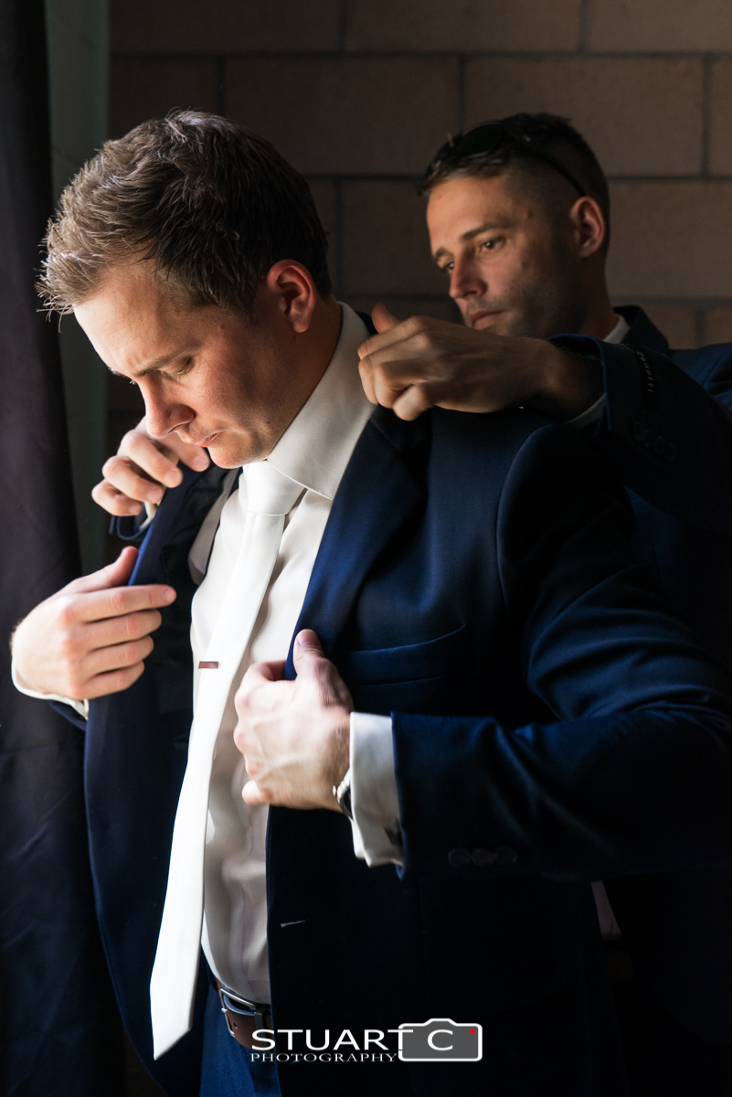 Groomsman helping the groom with his coat