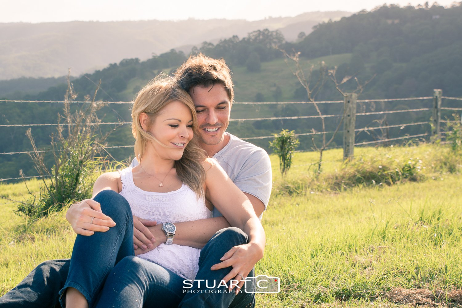 engaged couple sitting in grass in rural setting with fence behind