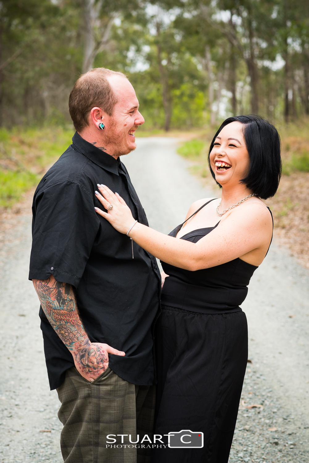 engaged couple standing on dirt road in bushland setting