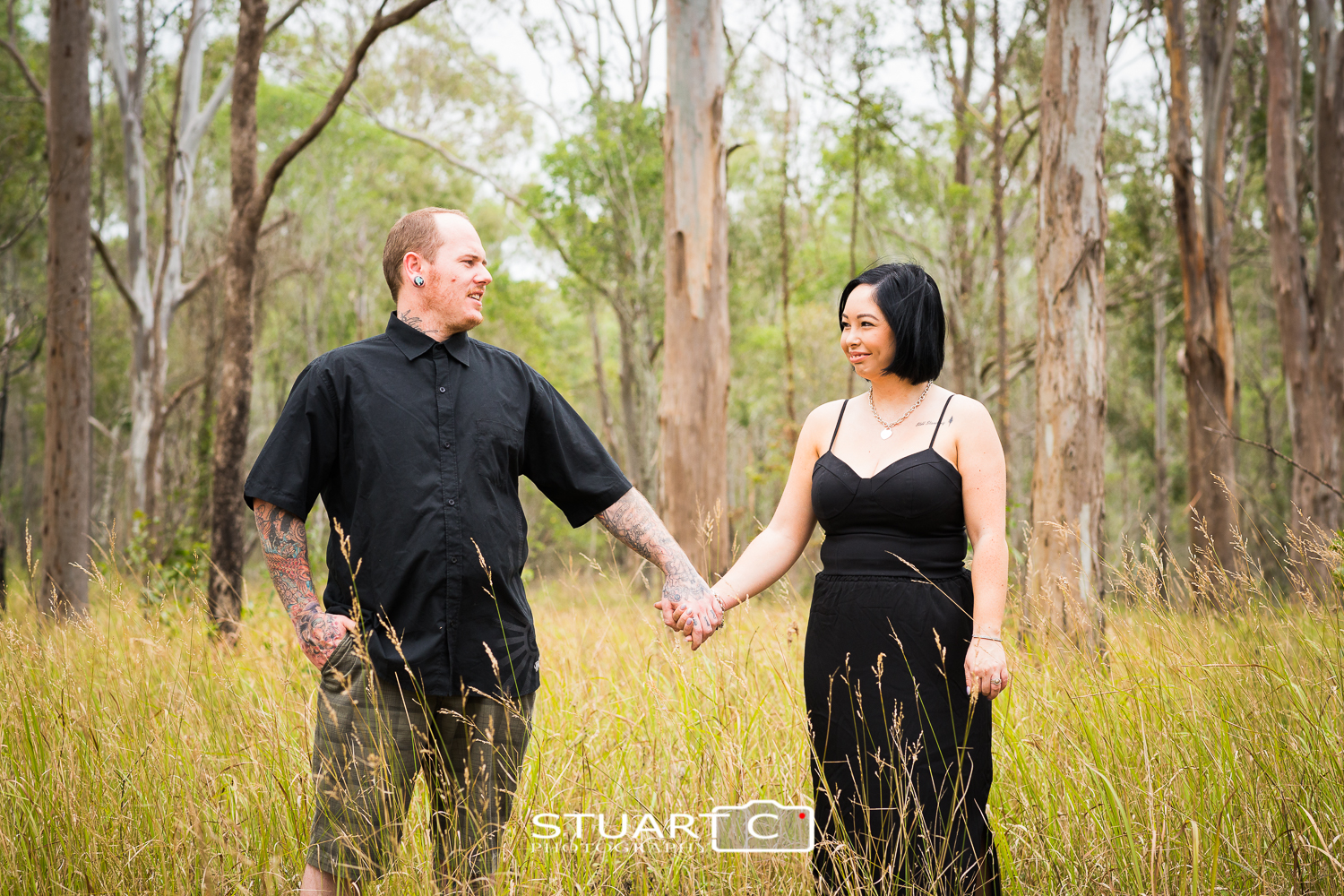 engaged couple standing in grass open bushland kurwongbah