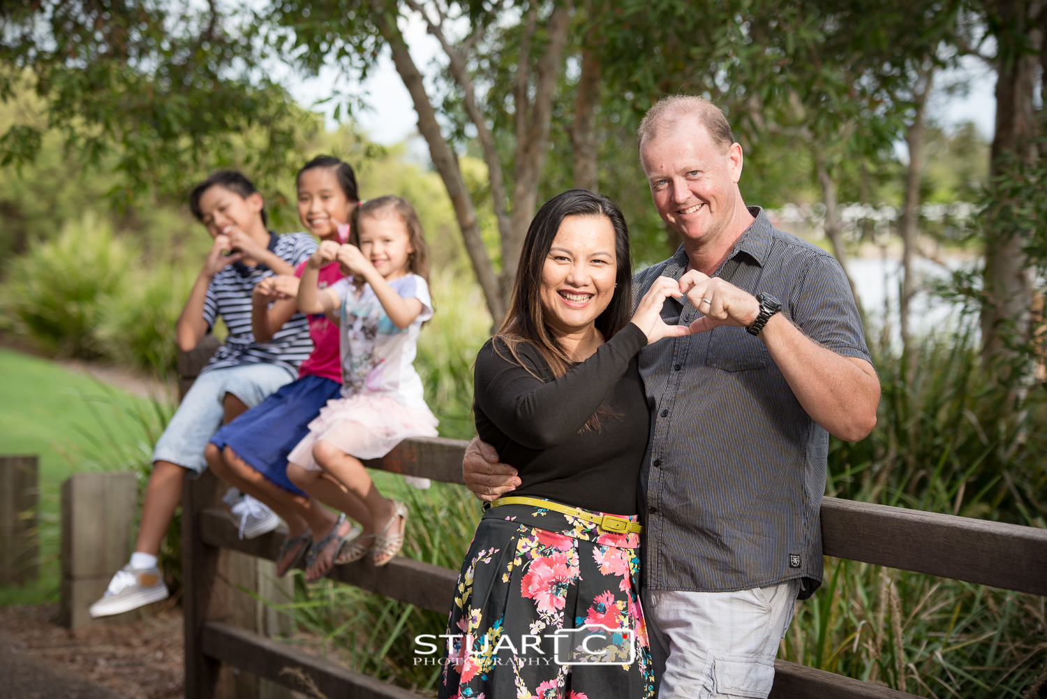family making heart shapes with hands at lake eden north lakes