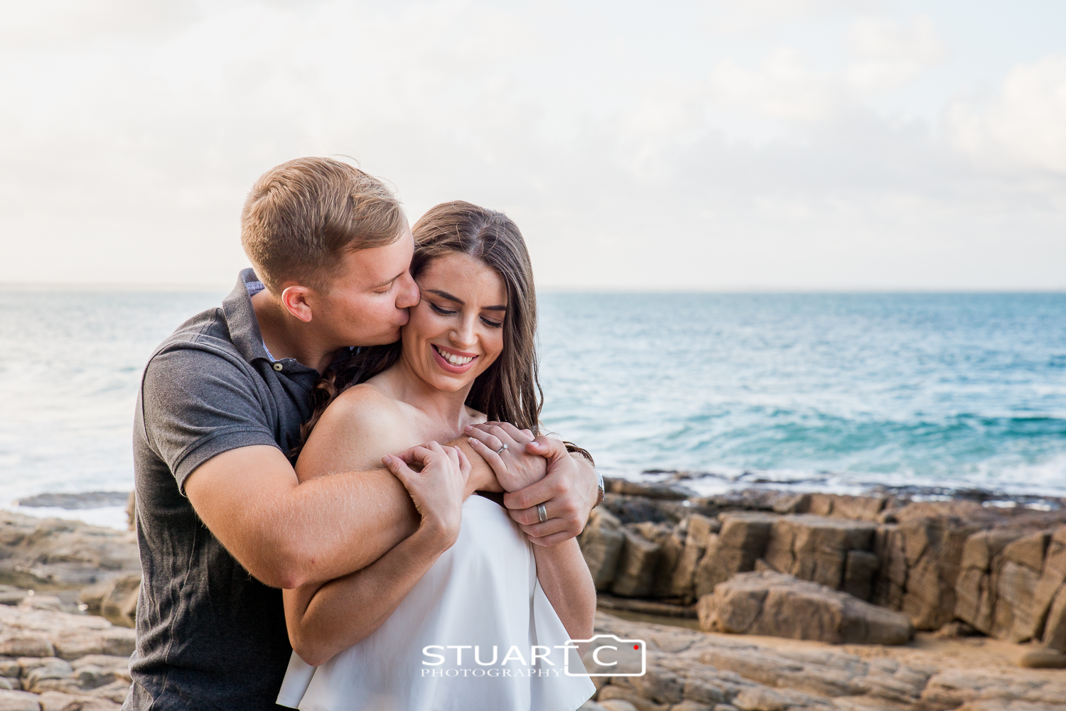 engaged couple at noosa beach on rocks
