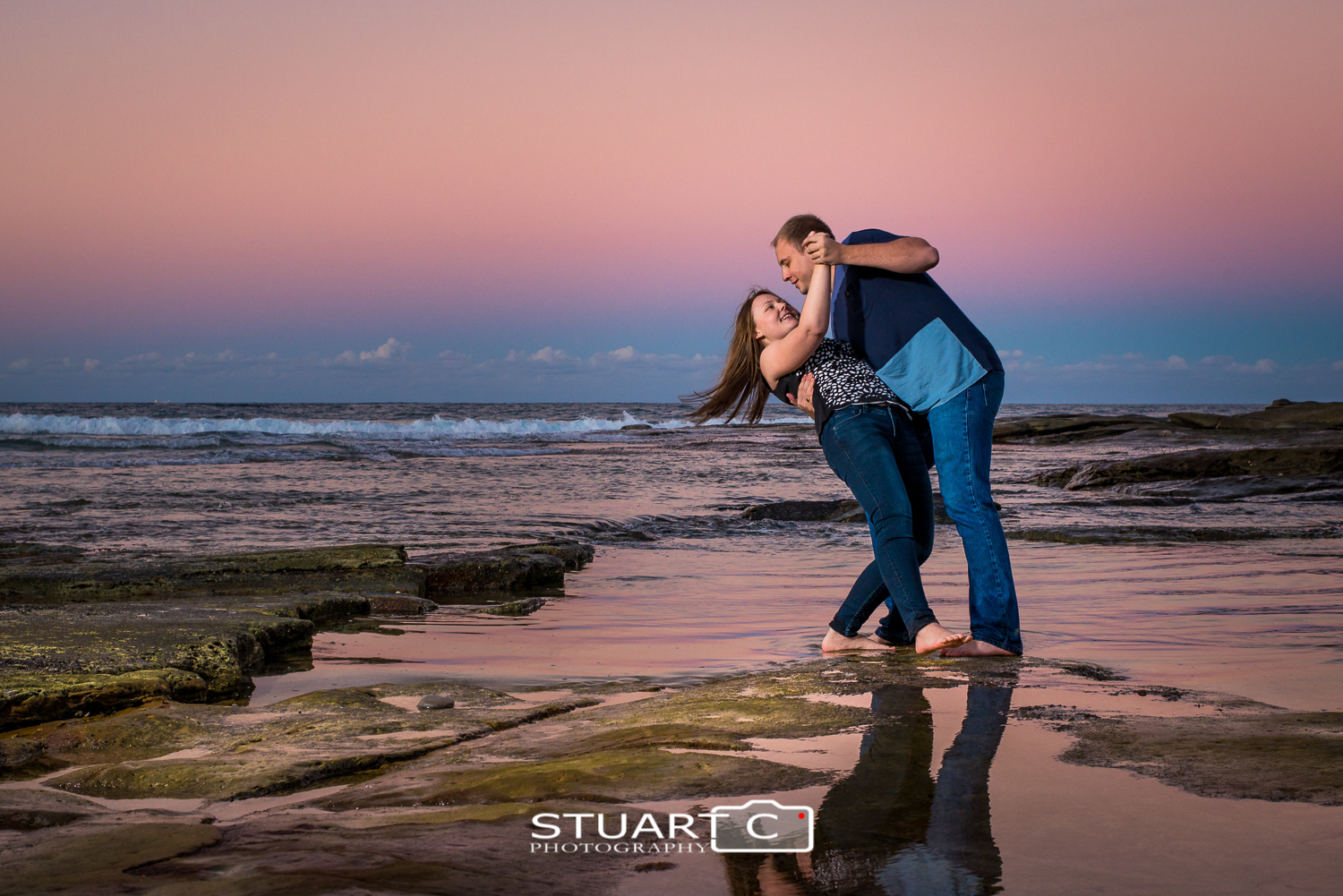 engaged couple dicky beach rocks sunset with flash