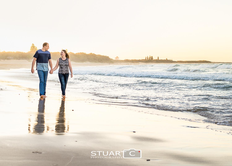 engaged couple walking along dicky beach caloundra at sunset