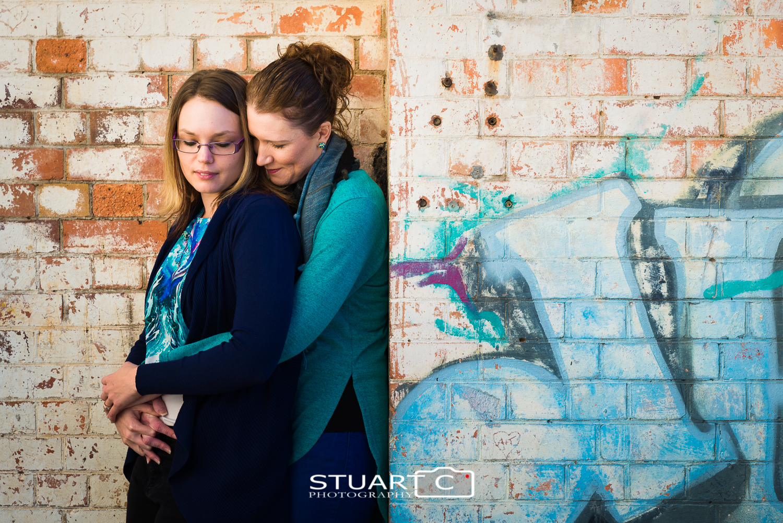 female couple against brick wall with grafiti