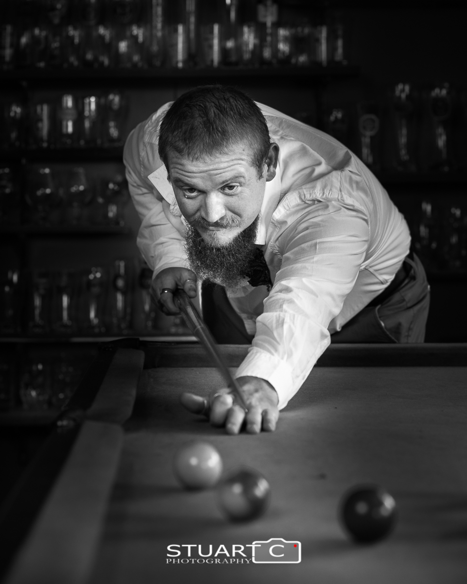 Groom lining up shot on pool table inside barn before home wedding at Elimbah