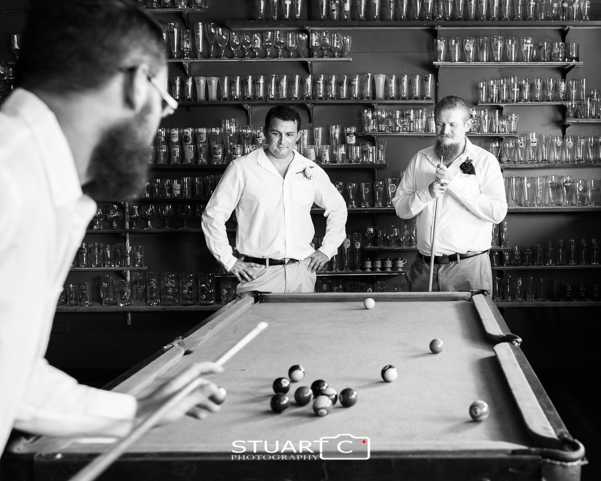 Groom and groomsman playing pool inside barn before home wedding at Elimbah