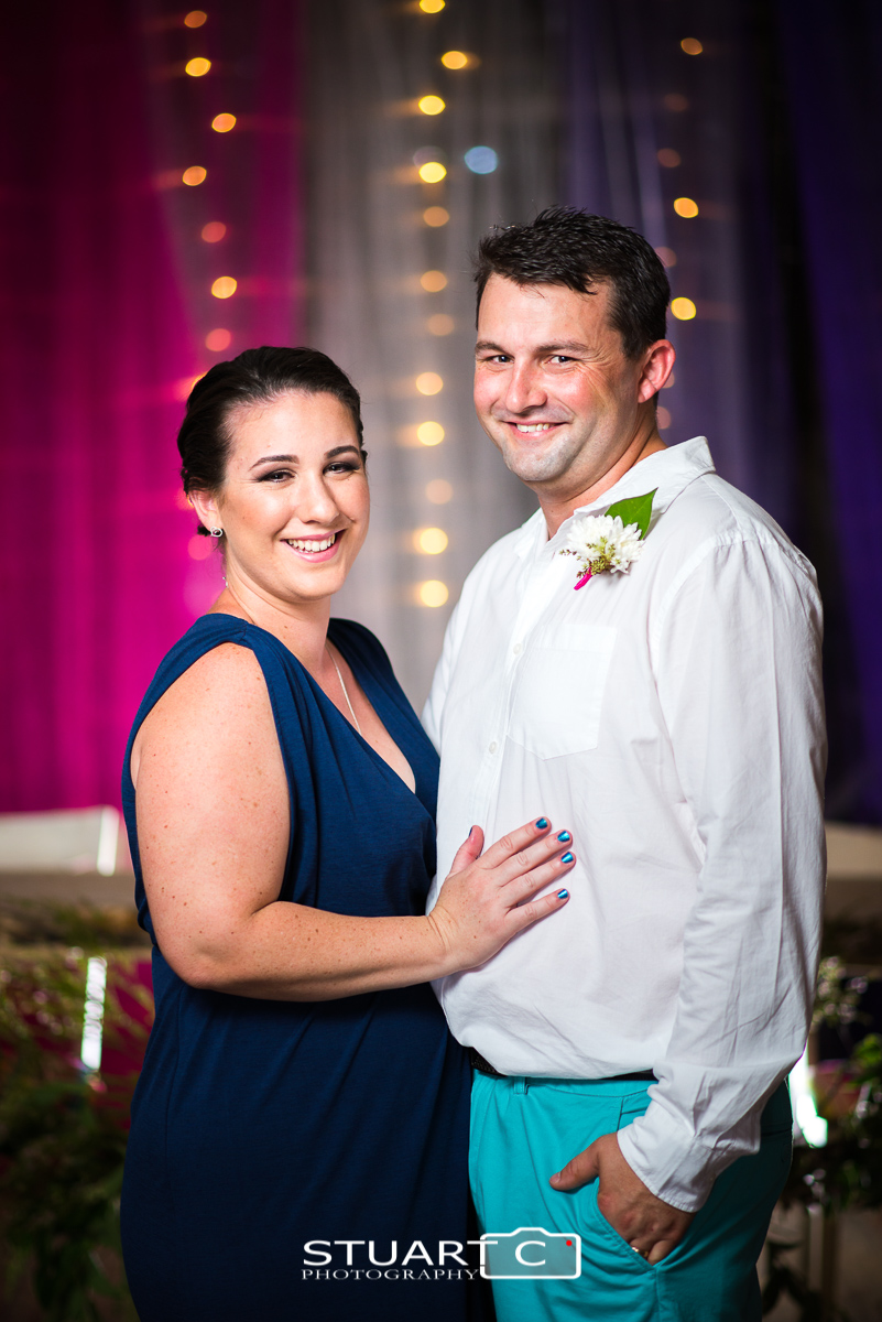 Couple standing in front of blue and pink fabrics with fairy lights inside rustic barn before home wedding at Elimbah