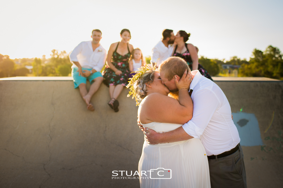Bride and groom in skatepark with wedding party on ramp behind at skatepark in elimbah