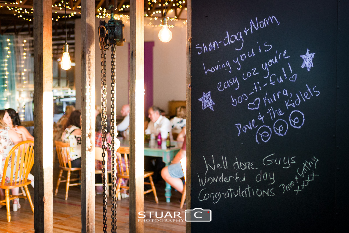 Messages of love from wedding guests written on the wall inside rustic barn reception at home in Elimbah