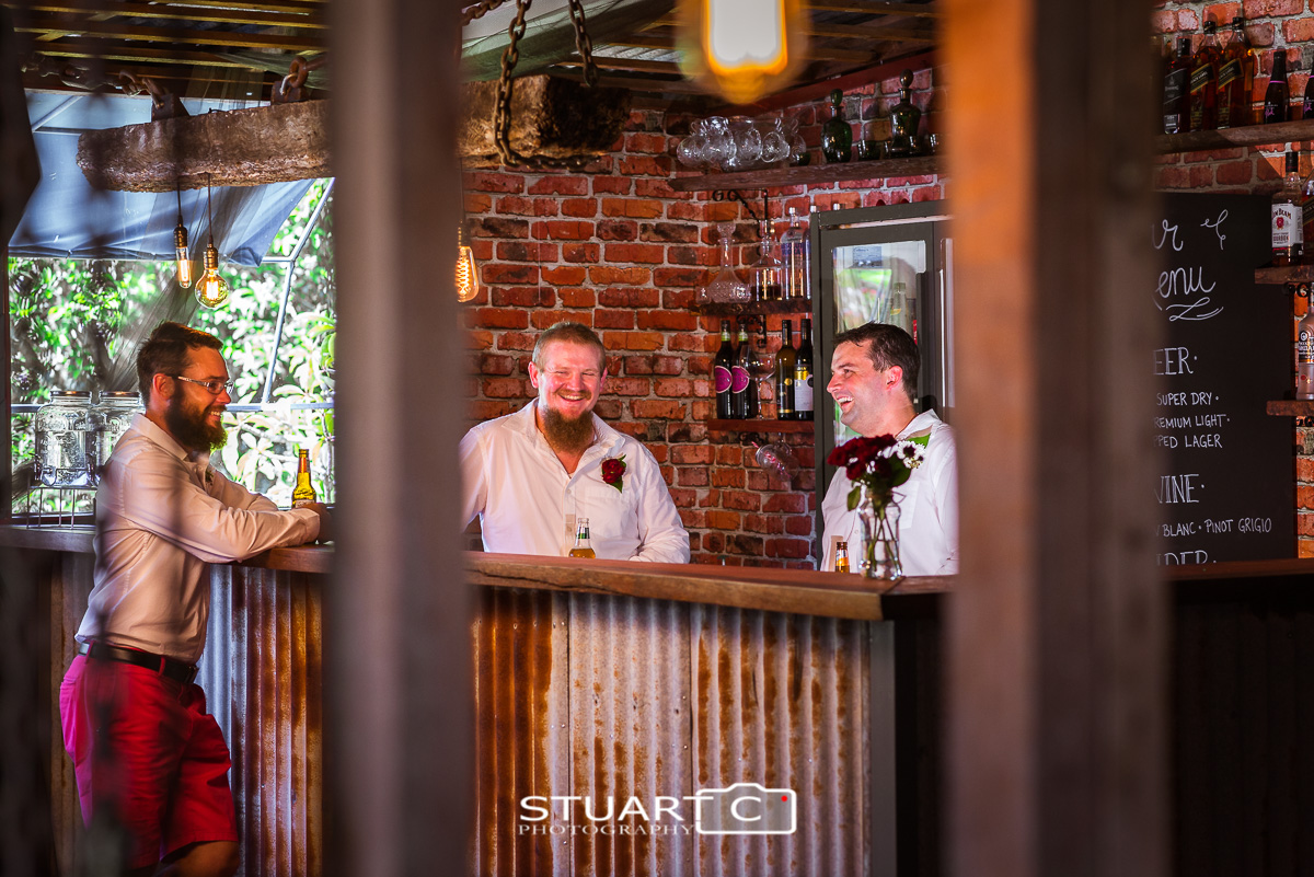 Groom and groomsmen at rustic bar inside barn before home wedding at Elimbah