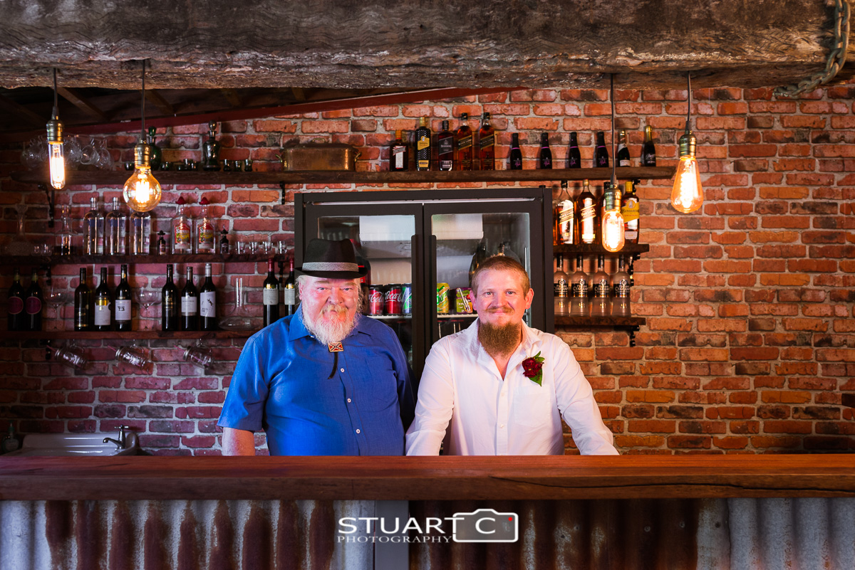 Groom and Father behind rustic bar inside barn before home wedding at Elimbah