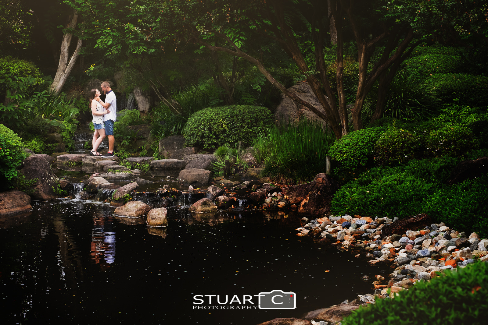 Casey and Gary standing on the rocky pathway in the middle of the Japanese Garden at Mt Cootha Botanical gardens during their engagement photo shoot