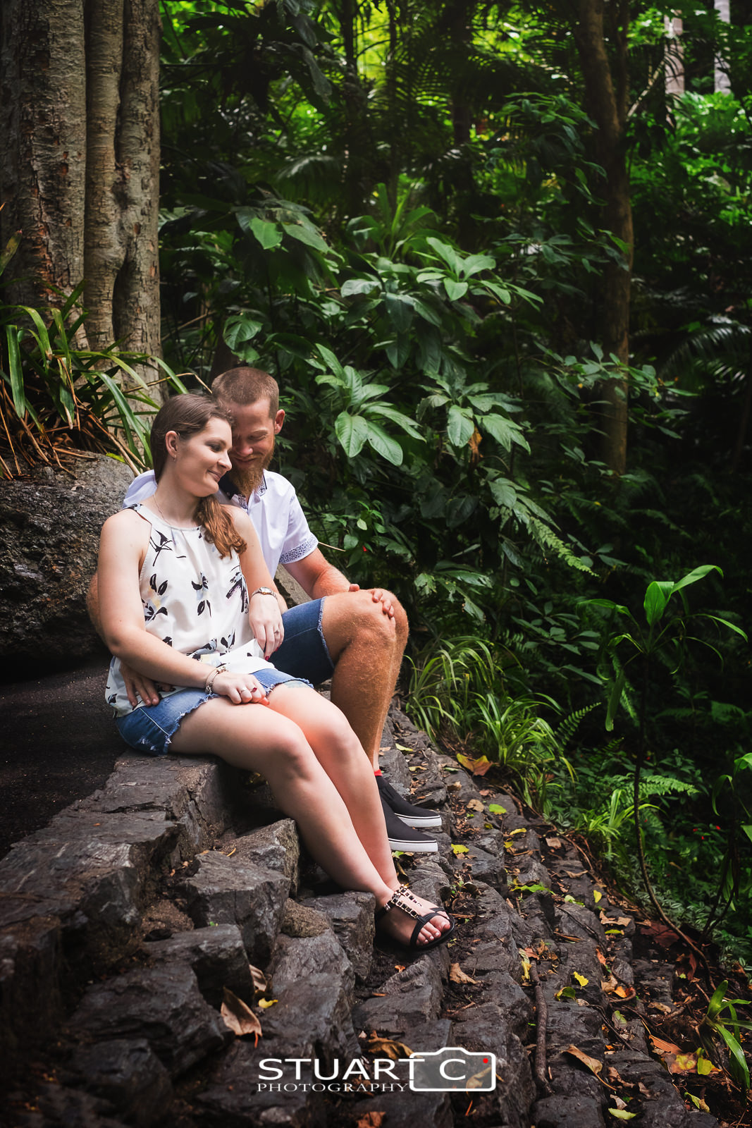 Casey and Gary sitting on a rocky step in among the dense rainforest of Mt Cootha Botanical gardens during their engagement photo session