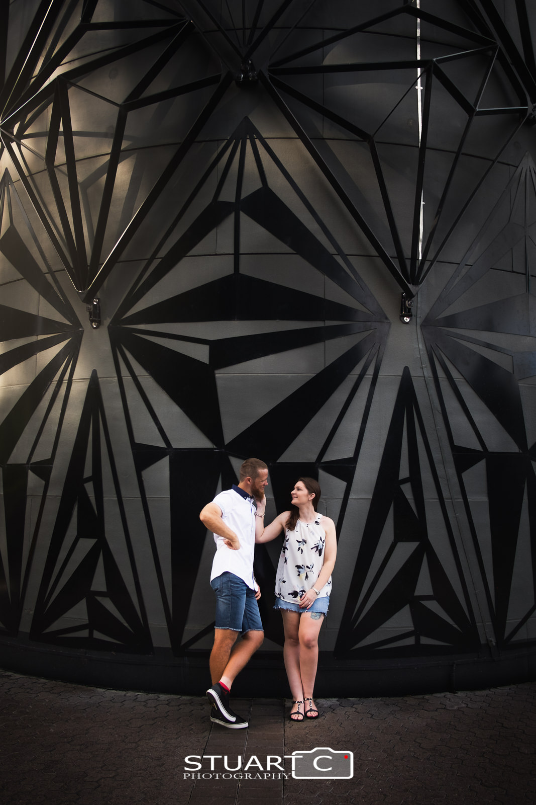 Portrait of newly engaged couple Casey and Gary standing in front of an urban art installation at Mt Cootha Botanical Gardens