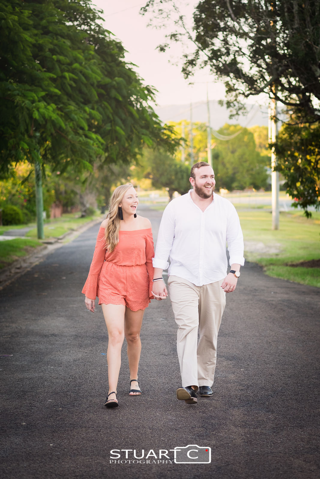 Full length Portrait of newly engaged couple Jannika and Matt walking along the street in Woodford