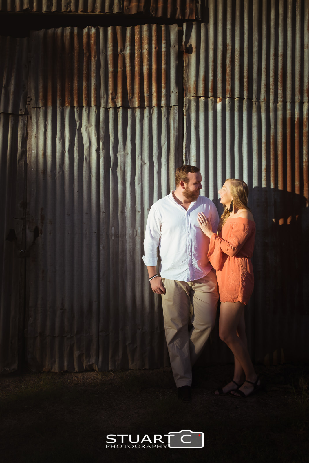 Urban rustic Portrait of newly engaged couple Jannika and Matt in the warm afternoon sunlight standing against rusted tin wall near the main street of woodford.