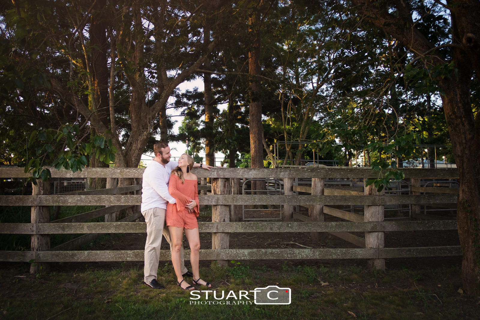 Country rustic Portrait of newly engaged couple Jannika and Matt leaning against the stock yard fence in woodford