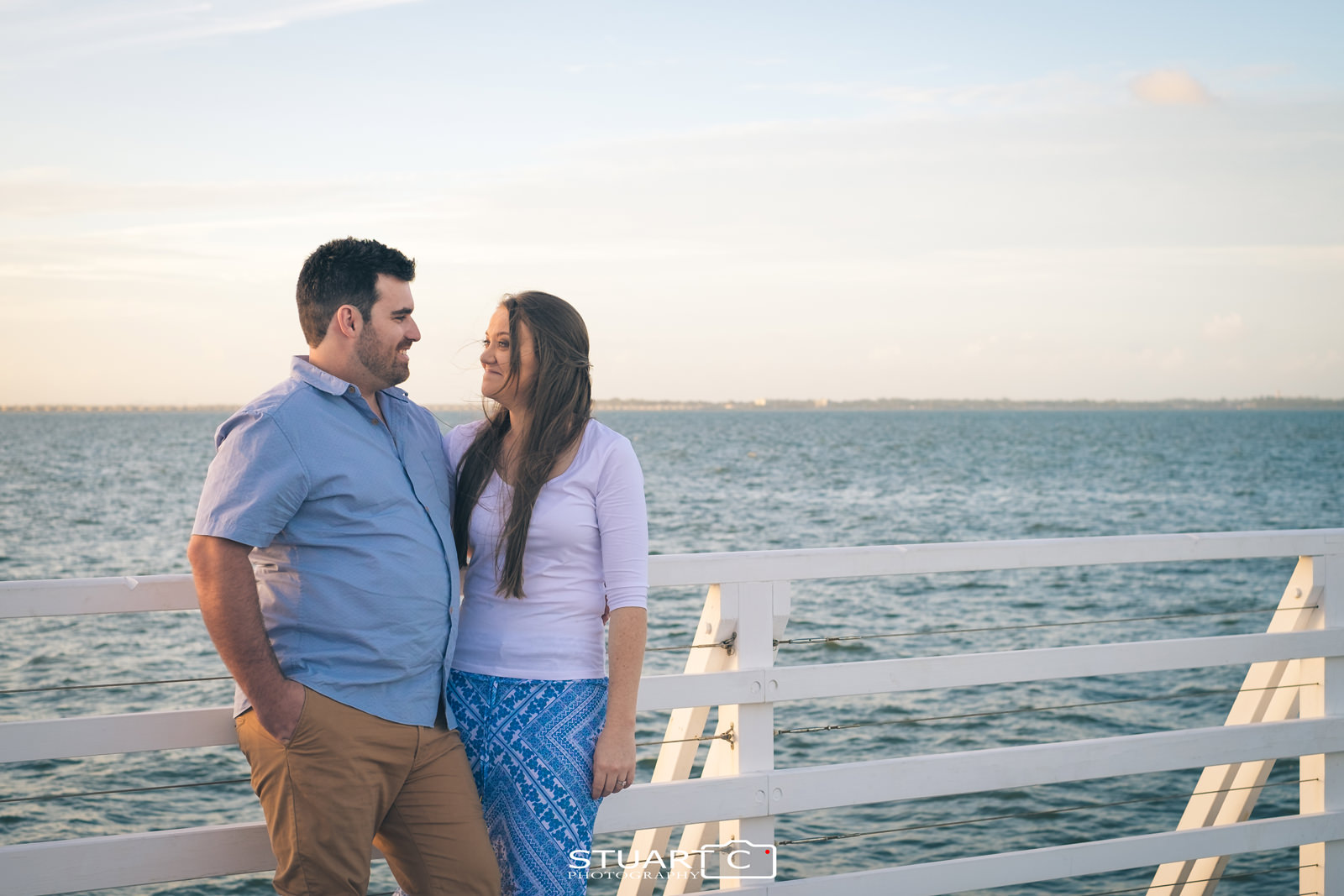 Portrait of engaged couple casually standing against white handrails on Shorncliffe Pier with warm golden sky behind