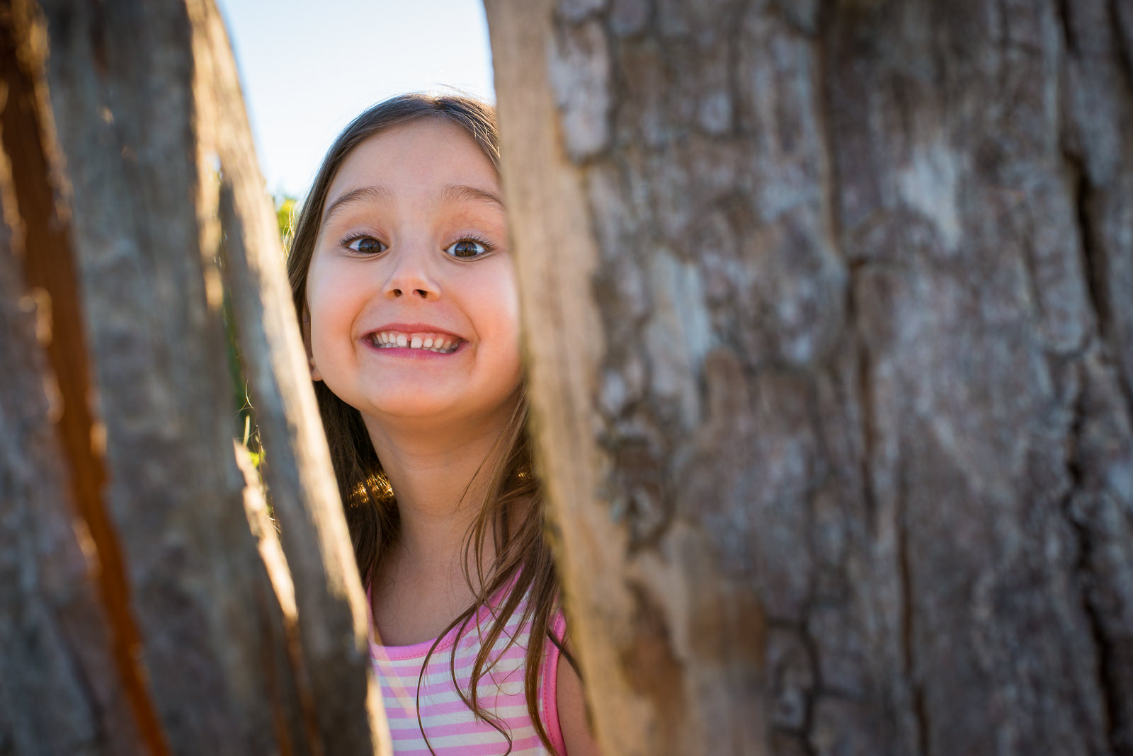 candid portrait of child looking through trees on a beach at bribie island near caboolture