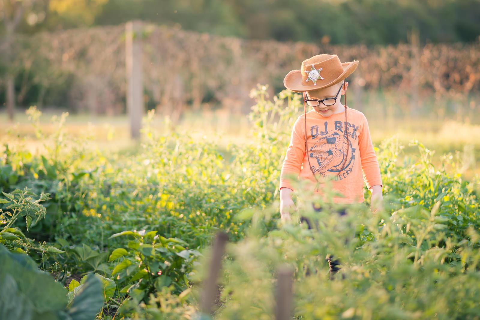 Portrait of little cowboy standing in vegetation in a rural setting in elimbah