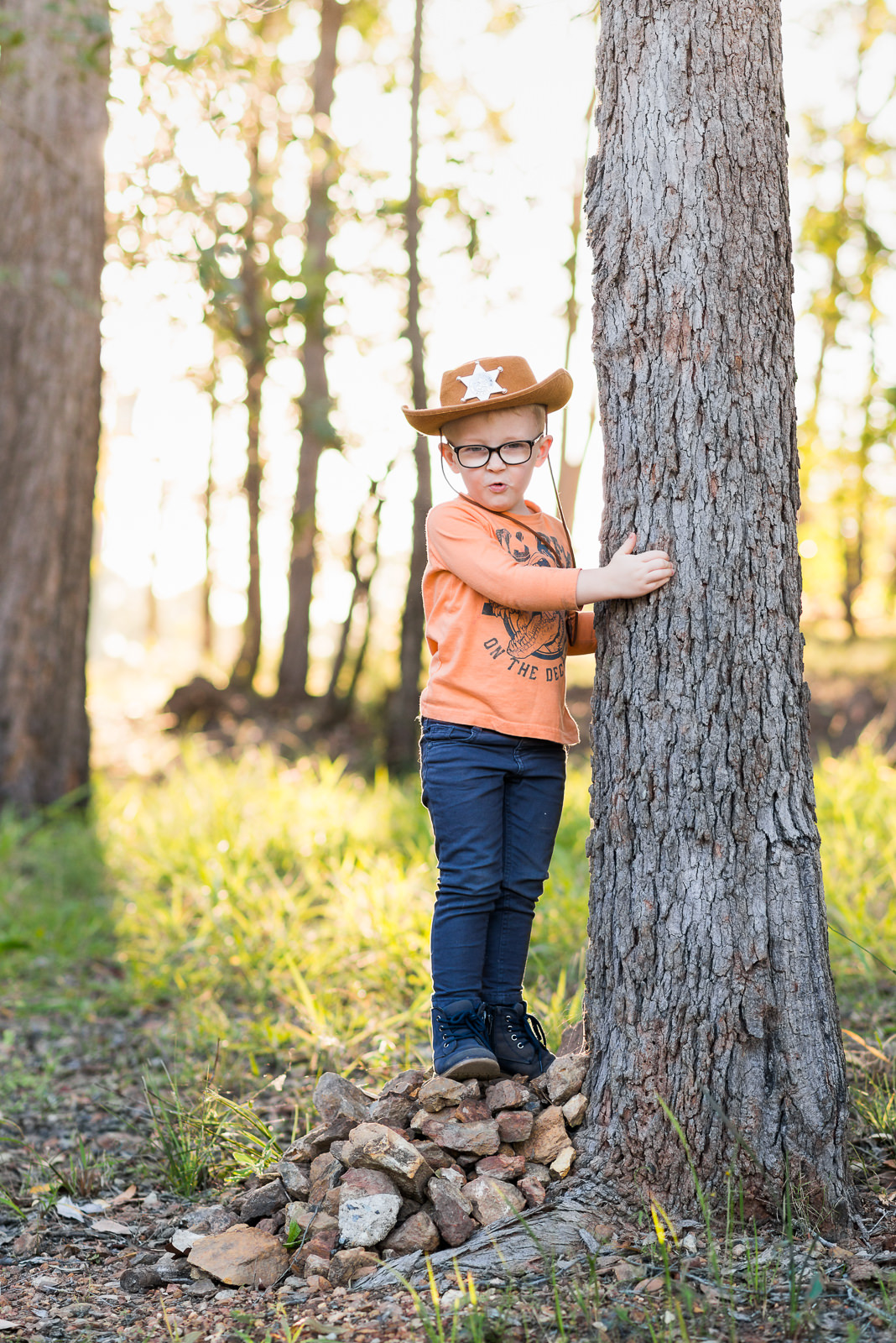 Portrait of little cowboy standing against a tree in a bushland rural setting in elimbah