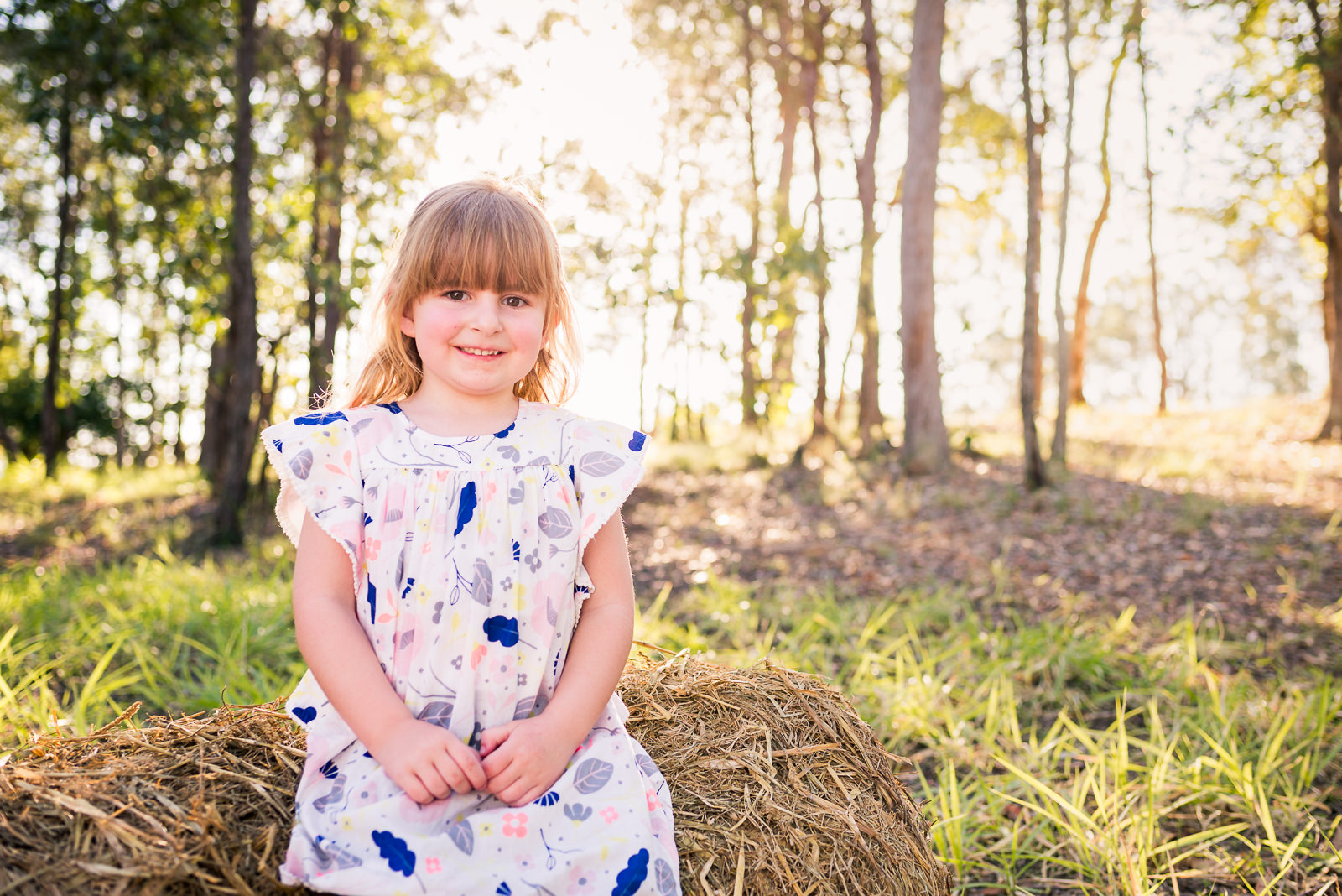 Portrait of little girl sitting on hay bale in a rural setting in Elimbah