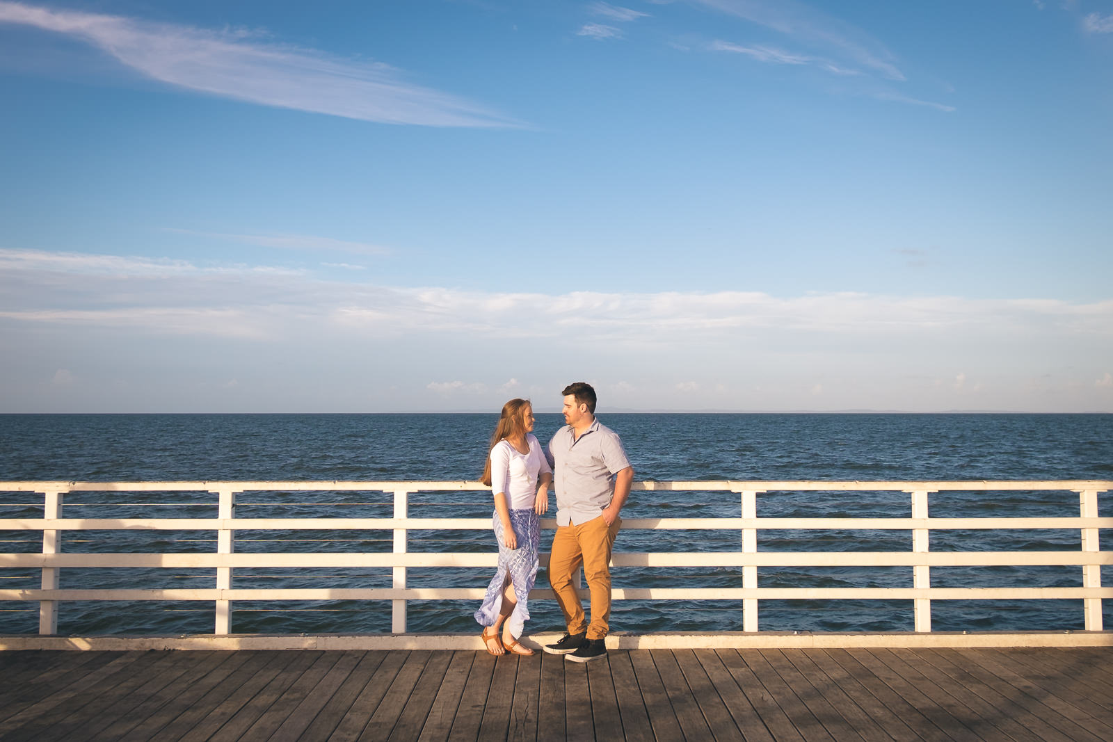 engaged couple standing at the end of Shornciffe pier later afternoon with deep blue sky