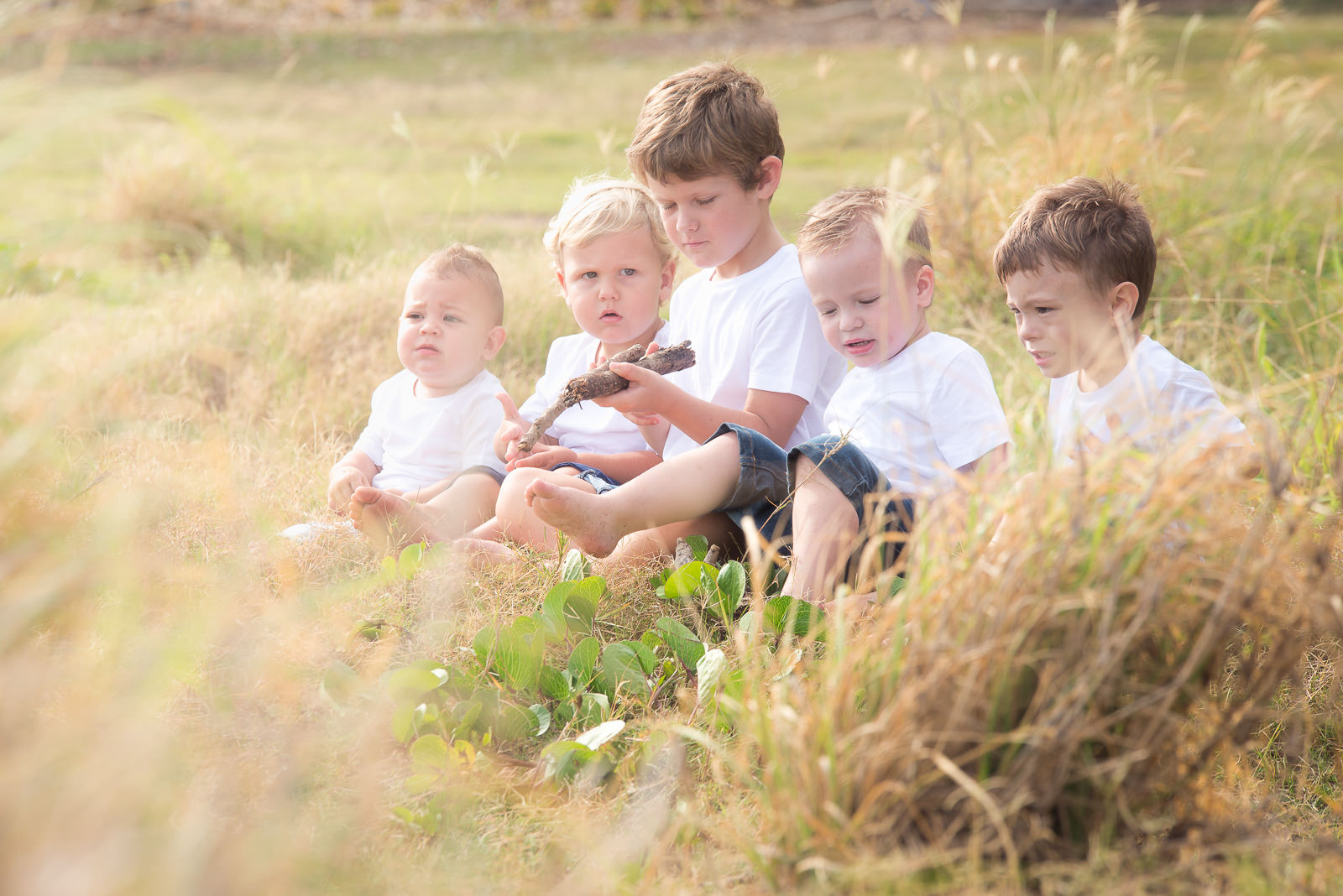portrait of young boys all cousins sitting in long grass near shorncliffe pier