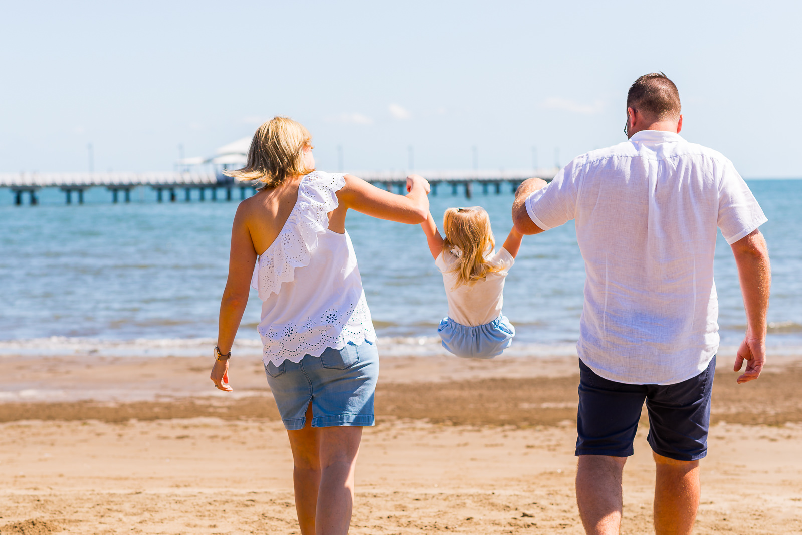 candid portrait of family of tree swinging child as they walk towards the water with shorncliffe pier in the background