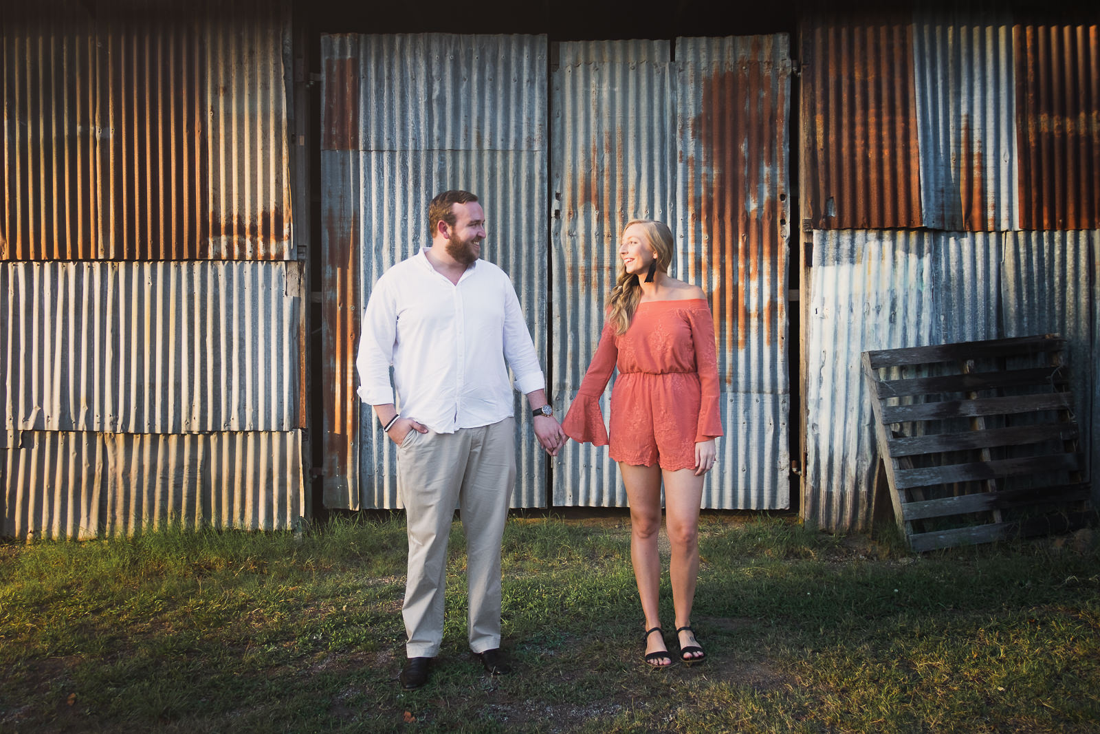 engaged couple standing in front of rusted tin wall in Woodford