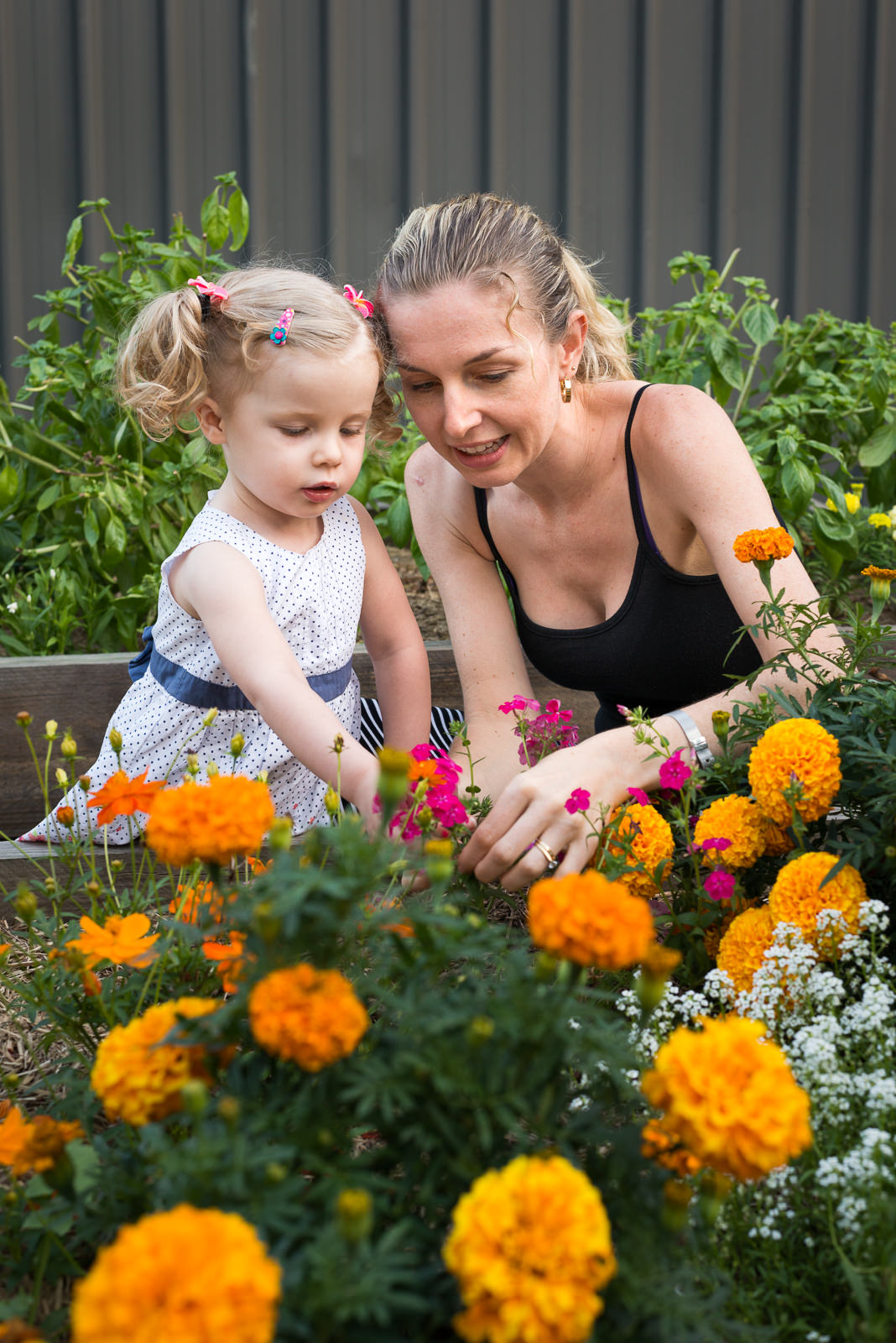 portrait of mother and daughter in the flower garden at home in Elimbah