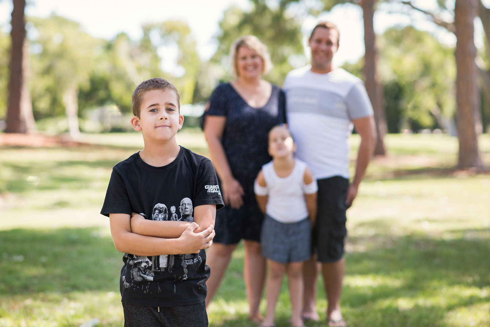 Family of four wearing white, blue and black combinations for outdoor family portraits in local park