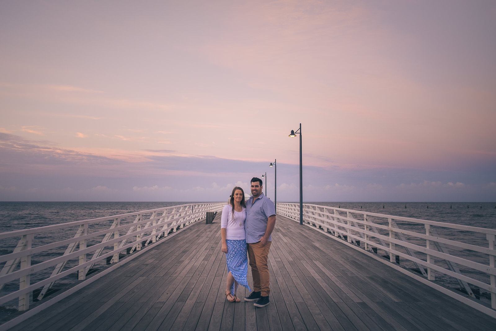 engaged couple standing on shorncliffe pier at sunset