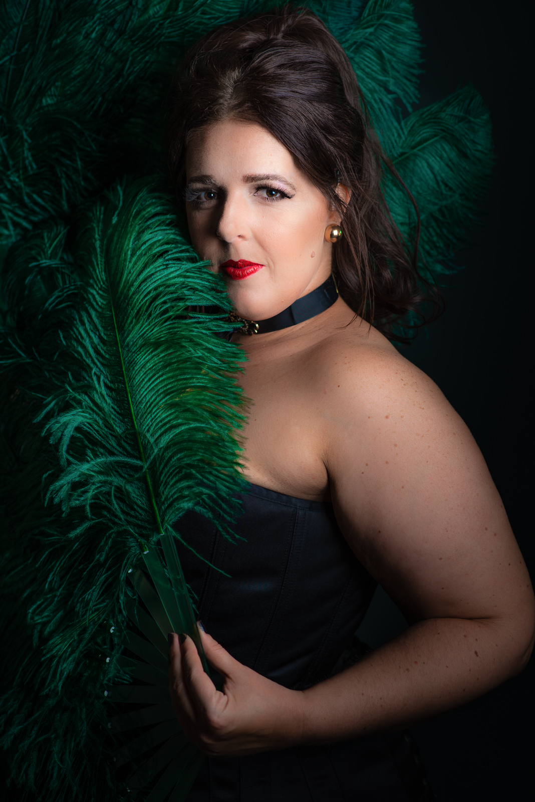 Up close portrait of Cora Confetti burlesque performer wearing black corset and holding green feather fans. Caboolture portrait photography