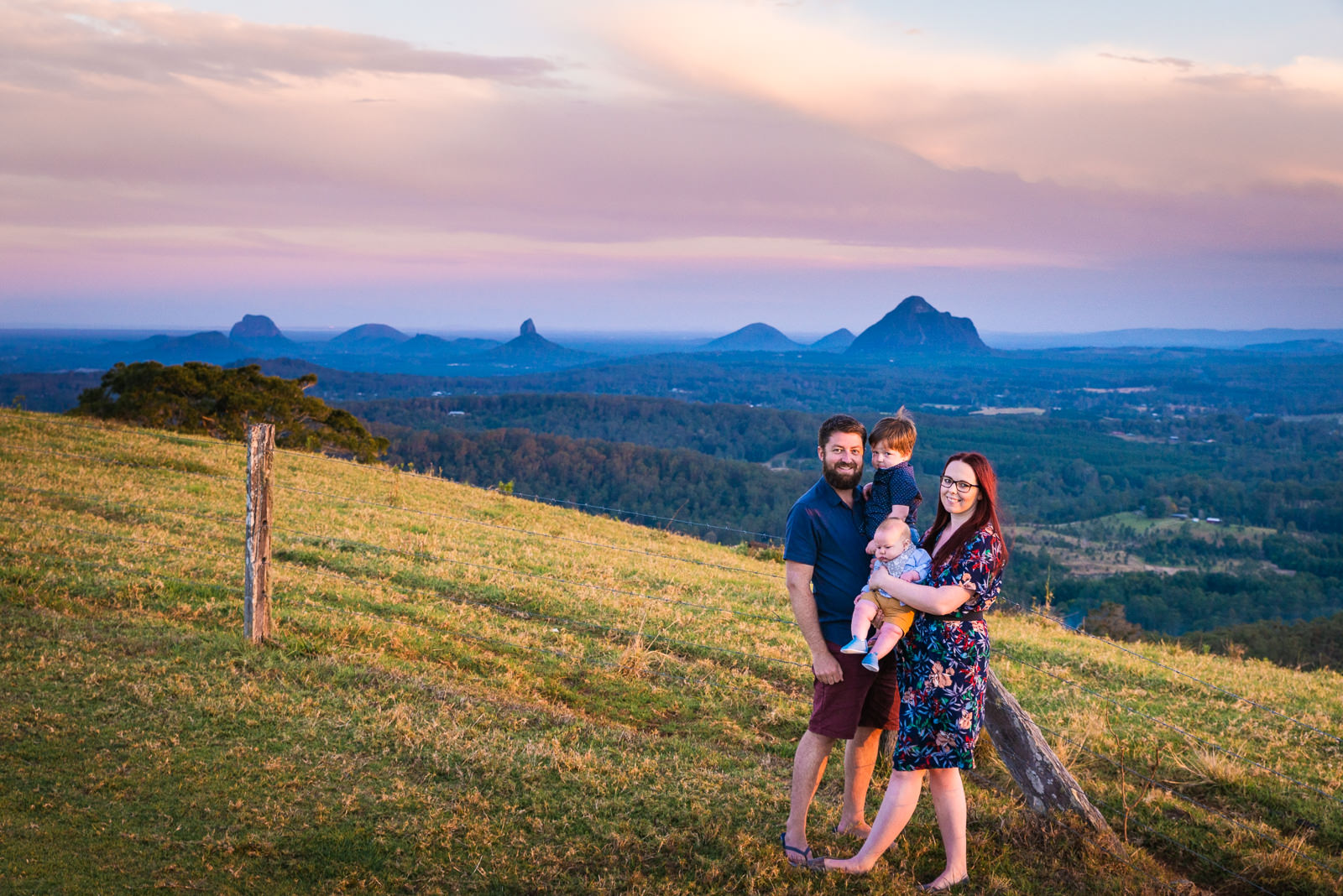 Family portrait at sunset overlooking the glass house mountains from Maleny in teh sunshine coast hinterland