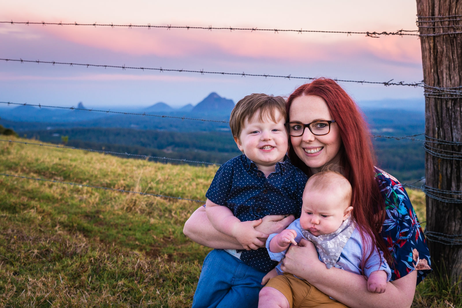 Mum and kids sitting down in rural setting overlooking the glass house mountains at sunset