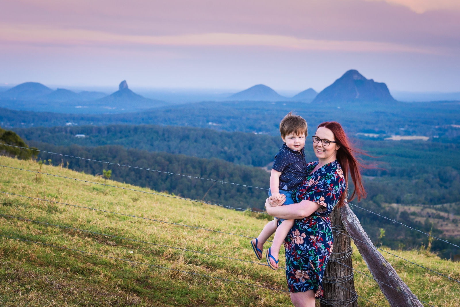 Mother and son with the glass house mountains in background at sunset
