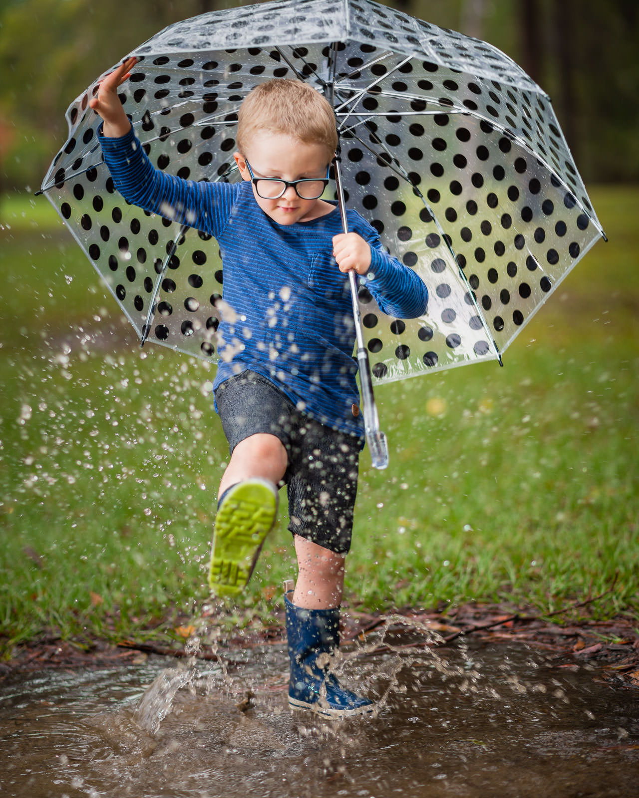 Young boy splashing in puddles in the park with a big clear umbrella as it rains | caboolture outdoor family photographer