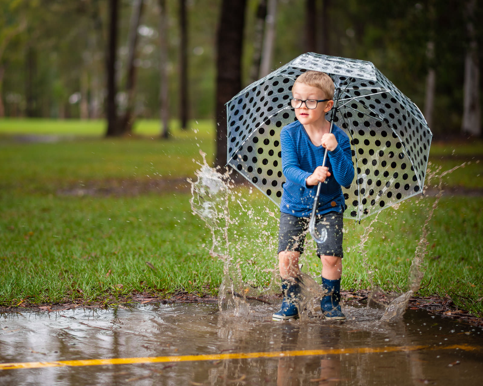 Young boy jumping and splashing in puddles during outdoor portrait photos | Caboolture family photography