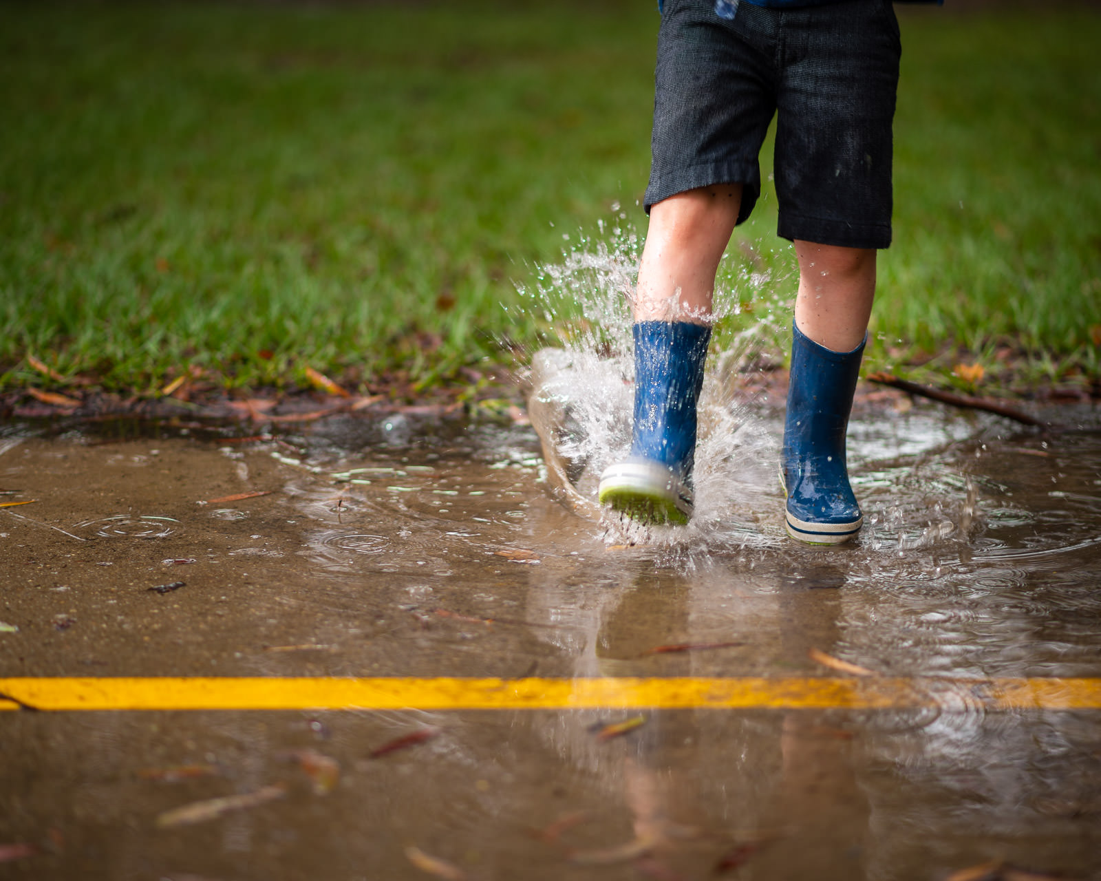 Close up of boys gumboots splashing in water | Caboolture outdoor family portraits