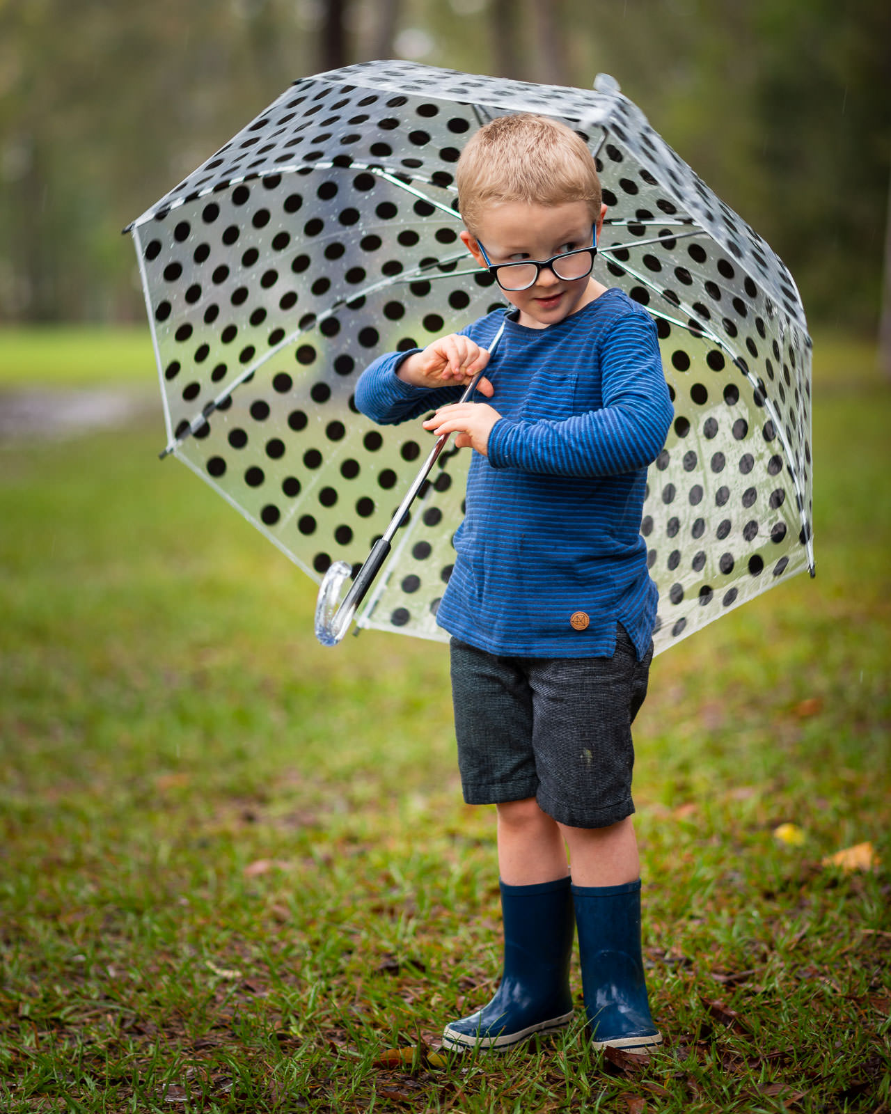 Portrait of child wearing gumboots and holding an umbrella as it rains in a caboolture park | North Brisbane family portrait photographer