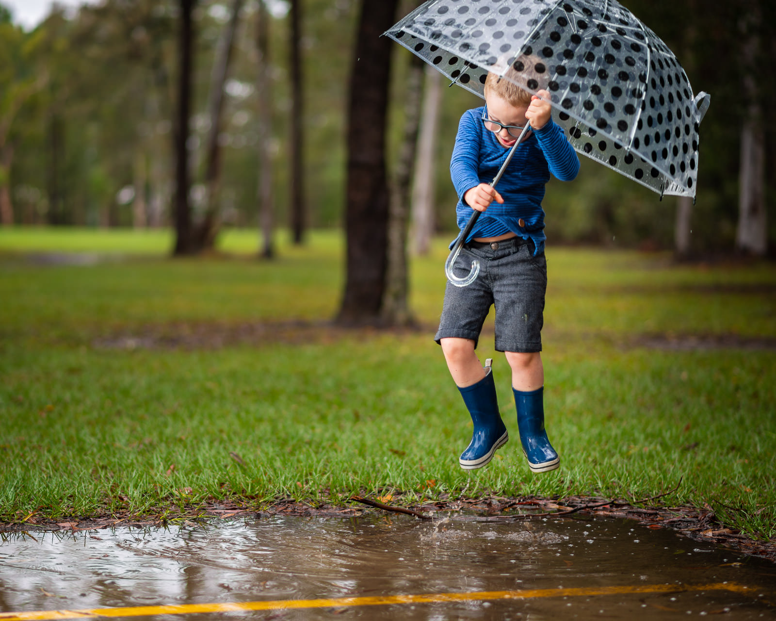 Jumping high in the air splashing in puddles during outdoor family portrait session in the rain | Caboolture family portraiture