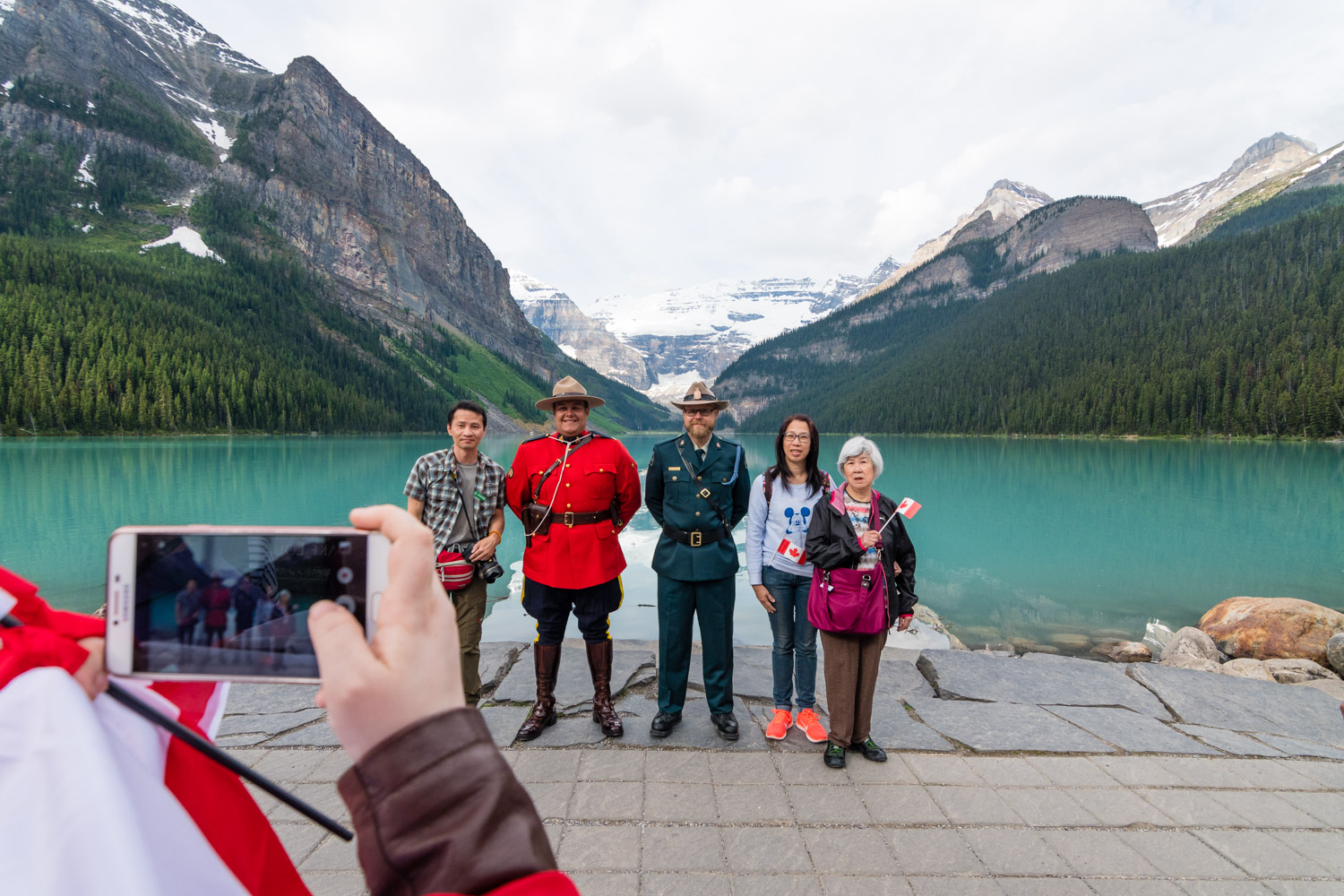 Tourists having a photo with Mounties of different flavours.