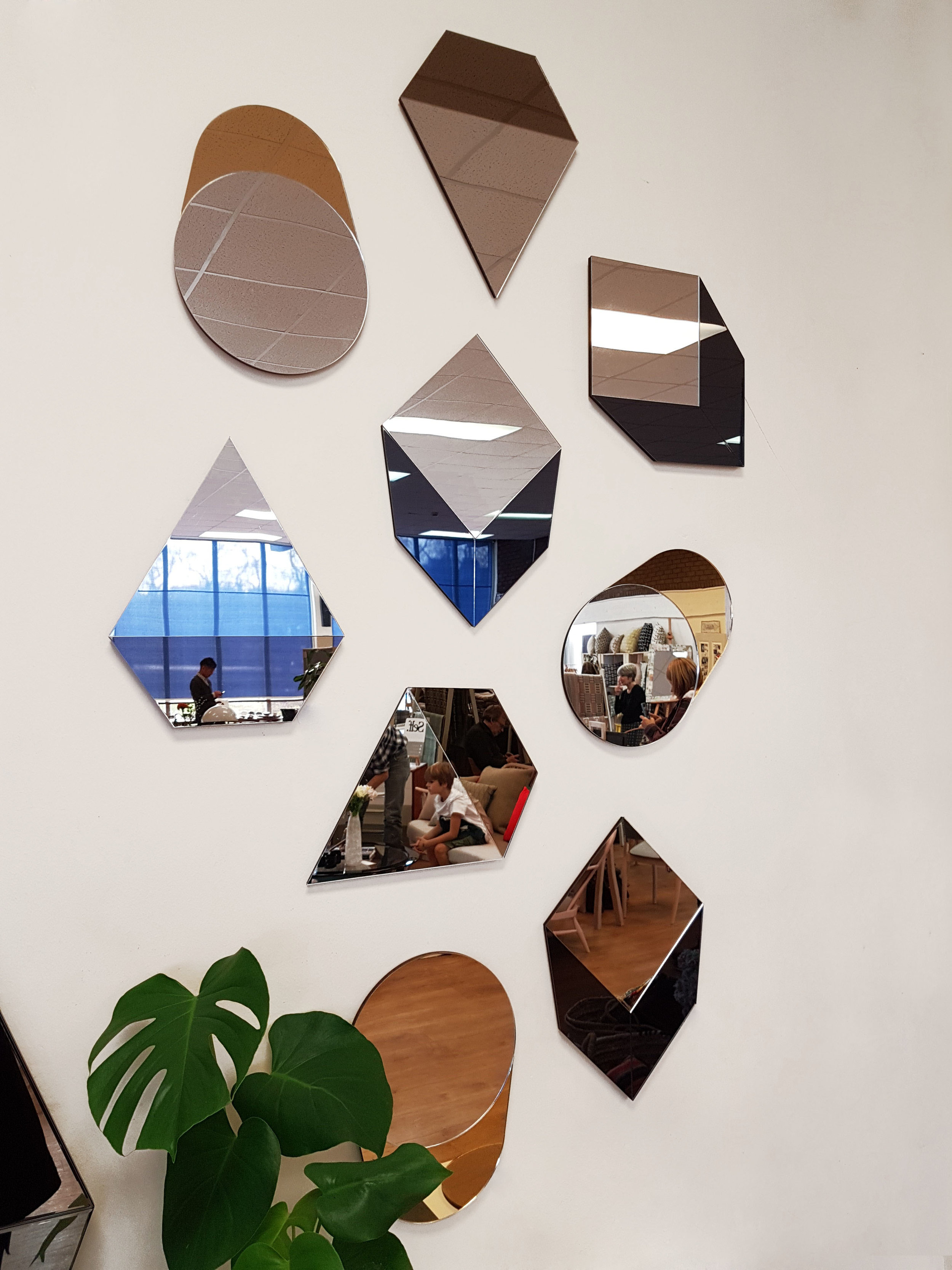 GEO MIRRORS - Mirror wall created from the GEO Mirror Collection, Prism, Cube and Cylinder are hung from one of three keyhole hangers to transform the metallic gallery wall design.